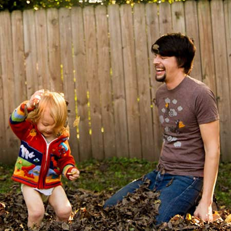Winston and his son playing in a pile of leaves